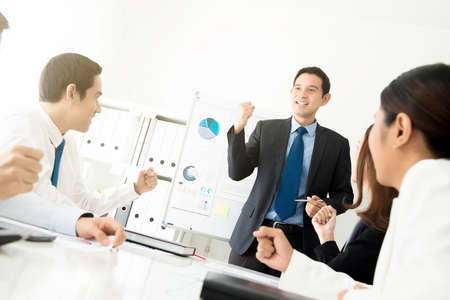 Powerful businessman as a meeting leader clenching his fist empowering his colleagues in front of the room Stock Photo