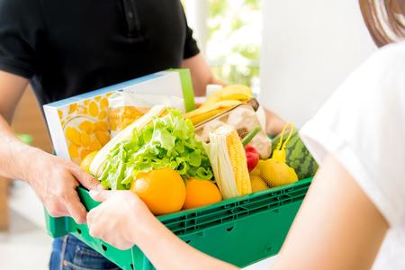 집에서 여자에게 음식을 배달하는 배달 남자 - 온라인 식료품 쇼핑 서비스 개념