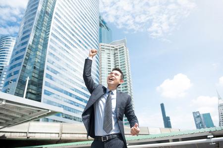 미소하고 그의 주먹을 공기 - 성공, 업적 및 승리 개념을 제기 사업가