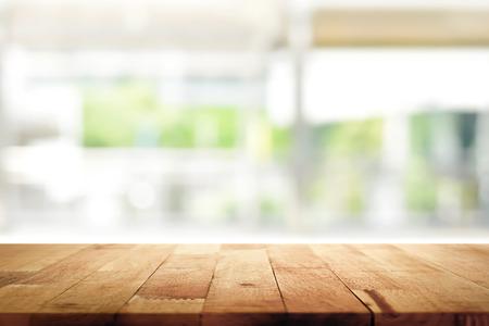 Houten tafelblad op vervagen keuken venster achtergrond - kan worden gebruikt voor weergave of montage van uw producten (voedingsmiddelen) Stockfoto