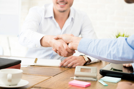 handclasp: Casual businessmen making handshake at  working table in the office