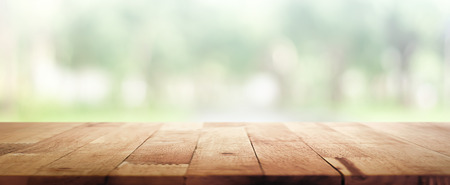 Wood table top on blur green panoramic banner background of trees in the park - can be used for display or montage your products