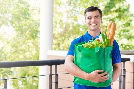 배달 사람이 안에 식료품 쇼핑 가방을 들고 미소 짓는 사람 스톡 콘텐츠