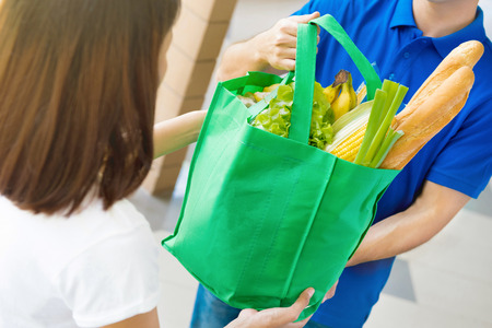 Delivery man giving grocery bag to a woman - food shopping service concept Stock fotó