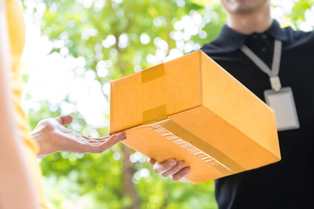 Delivery man delivering package to customer, close up at hand and box Stock Photo