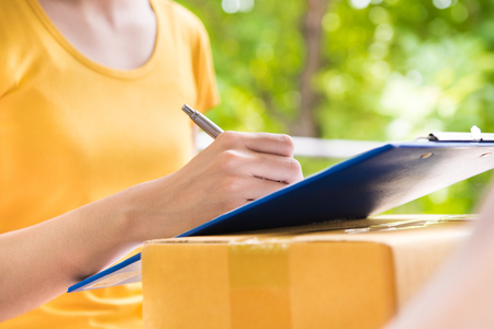 Young woman signing document while receiving package - courier and delivery service concepts Stock Photo