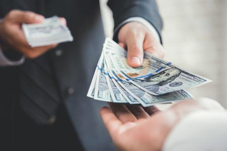 Homme d'affaires donnant ou payant de l'argent à un homme, billets en dollars américains - prêts, corruption et concepts financiers Banque d'images - 81597720
