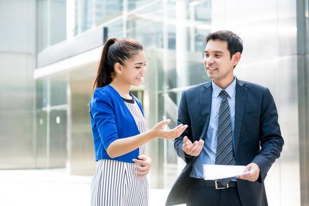 아시아 비즈니스 사람들이 사무실 건물 앞에 야외에서 산책하는 동안 문서를 논의