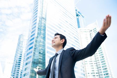 Businessman raising his arms opening palms with face looking up, in office building background - happy, success and achievement concepts