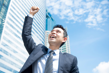 Businessman smiling and raising his fist in the air in office building background - business success and achievement concepts