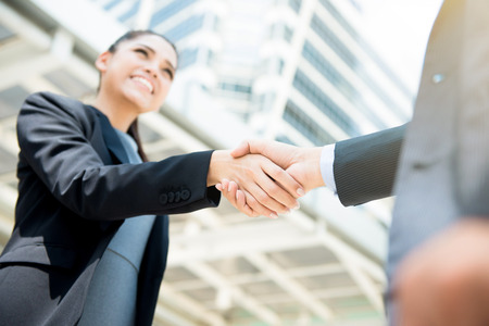 Businesswoman making handshake with a businessman - female leader concept Stock Photo