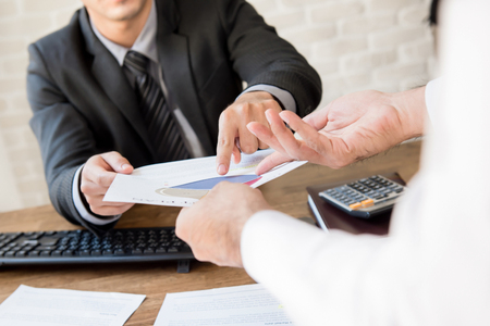 Businessmen discussing financial document at working desk
