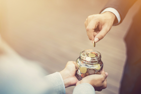 Businessman hand putting money (coin) in the glass jar held by a woman, vintage tone effect