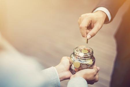 Main d'homme d'affaires mettant de l'argent (pièce de monnaie) dans le bocal en verre tenu par une femme Banque d'images