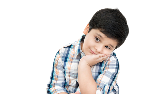 Smiling cute Asian boy with hand on cheek - isolated on white background Foto de archivo
