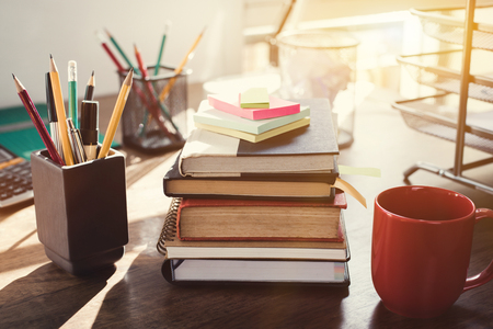 pen holder: Stack of books and stationery on the desk - vintage tone effect