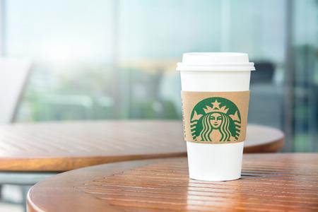 BANGKOK, THAILAND - JUN 29, 2016 : Starbucks take away coffee cup on wood table in Starbucks coffee shop