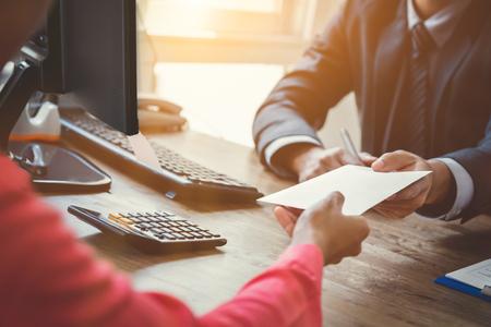 Zakenman die envelop (geld) van een vrouw ontvangen bij werkend bureau - omkoperijconcept