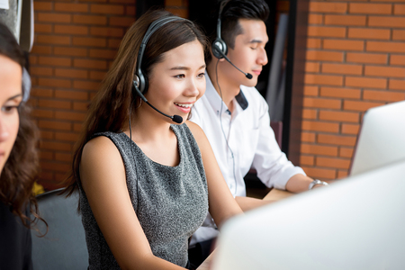 Smiling Asian businesswoman working in call center as  an operator or telemarketer Archivio Fotografico