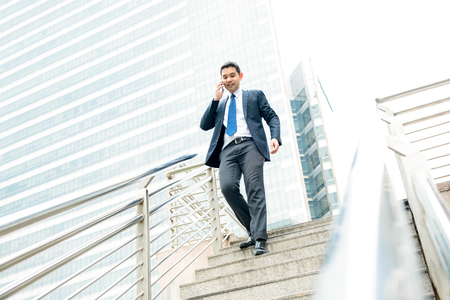 Businessman calling on mobile phone while walking down walkway bridge in the city