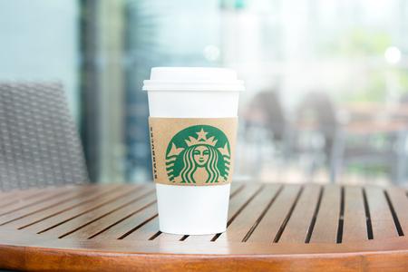 BANGKOK, THAILAND - JUN 29, 2016 : Starbucks take away coffee cup on wood table in Starbucks coffee shop Editorial