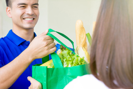 Smiling delivery man giving grocery bag to a woman - food shopping service concept