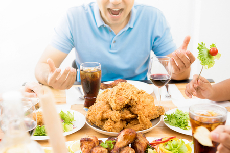 食べ物や飲み物に興奮して飢えた若い男の前でダイニング テーブルの上 写真素材