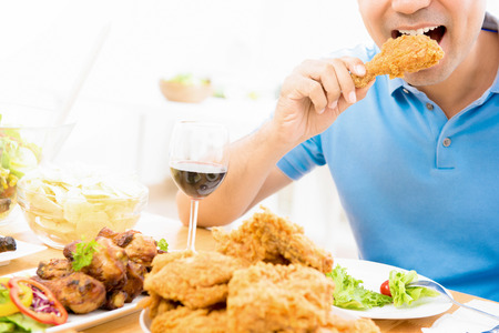 Young man eating fried chicken in the restaurant Imagens