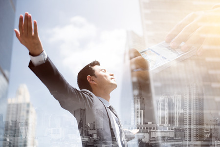 Success businessman in the city raising his arms, open palms, with face looking up - financial freedom concepts, double exposure effect