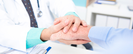 Doctor holding senior male patient hand with care - panoramic banner