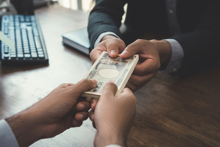 venal: Businessman giving money, Japanese yen banknotes, to his partner - payment, loan and bribery concepts Stock Photo