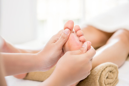 Professional therapist giving traditional thai foot massage to a woman in spa Stock Photo