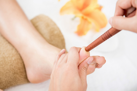 Therapist giving traditional thai foot massage with stick to a woman in spa