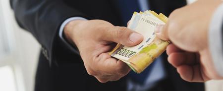 venal: Businessman giving money, South Korean won banknotes, to his partner, bribery concept - panoramic banner