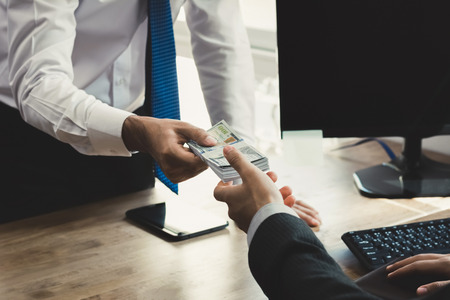 Businessman receiving money from his partner at working desk in the office - loan, bribery and corruption concepts Stock Photo
