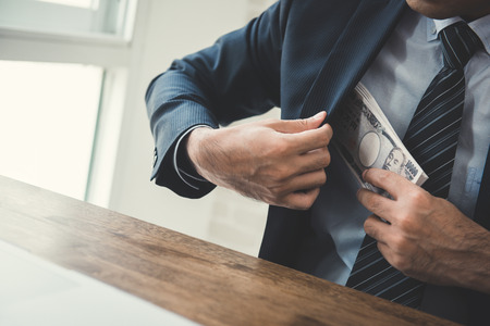 putting money in pocket: Businessman putting money, Japanese  yen banknotes, into his suit pocket - bribery and corruption concept Stock Photo