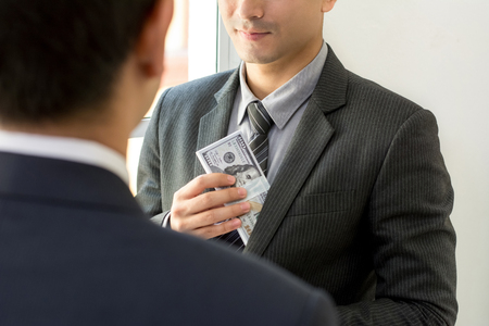 putting money in pocket: Businessman putting money into his suit pocket after making a deal with partner Stock Photo