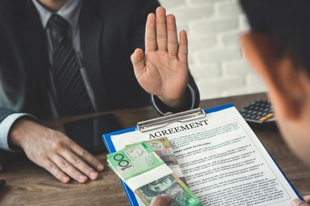 Uomo d'affari che rifiuta i soldi, dollari australiani, che vengono con il documento del contratto - anti corruzione e concetti di corruzione Archivio Fotografico - 83859999