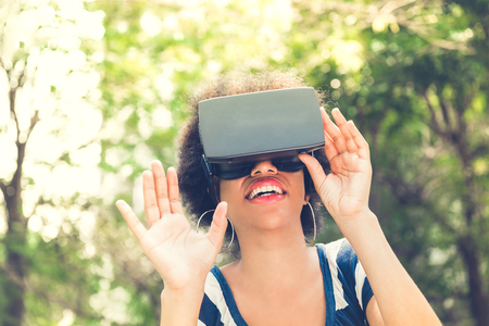 virtual reality simulator: Afro woman enjoying watching  3D simulation video from virtual reality (VR) headset - people and technology concept