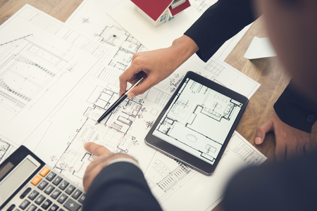Architects or interior designers discussing floor plan blueprints on the table Archivio Fotografico