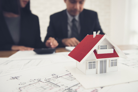 Real estate agent discussing work with blueprints and house model on the table - property appraisal and valuation concept Foto de archivo