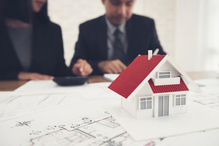 Agente de bienes raíces discutiendo el trabajo con planos y el modelo de la casa en la mesa - concepto de tasación y valoración de propiedad