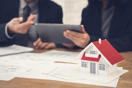 agente de bienes raíces con el cliente o equipo de equipo que discute el ordenador en la computadora de la tableta