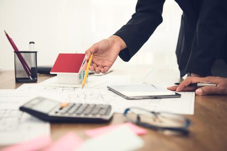 Immobilienmakler mit Kunden- oder Architektenteam, das auf dem Tisch Hausbodenplan bespricht