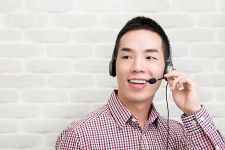 Casual Asian businessman wearing microphone headset  as a telemarketing customer service agent, call center job concept