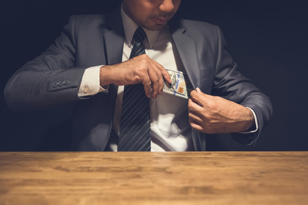Dishonest businessman putting money, US dollars, into his suit pocket in the dark - corruption and embezzlement concepts