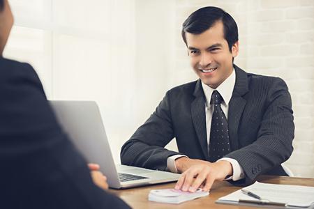 El astuto hombre de negocios astuto le da dinero a su compañero en la mesa de trabajo: conceptos de soborno, corrupción y venalidad
