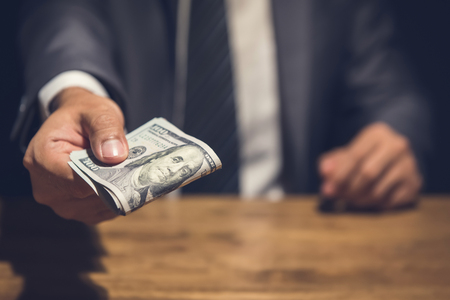 Dishonest businessman secretly giving away money in the dark - bribery, scam and venality concepts Archivio Fotografico