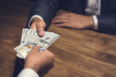 Zakenman die geld, Amerikaanse dollar (USD) rekeningen geven, aan zijn partner op de tafel in het donker - omkoping, corruptie en venality concepten