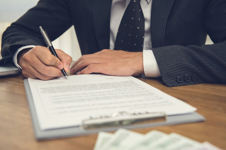 Businessman signing legal business contract agreement with money on the table Foto de archivo